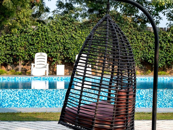 Wicker hanging chair outside of the Safe House Wellness Retreat India